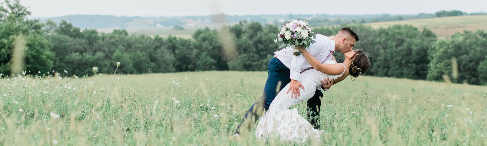 Bride and groom on sofa in a field
