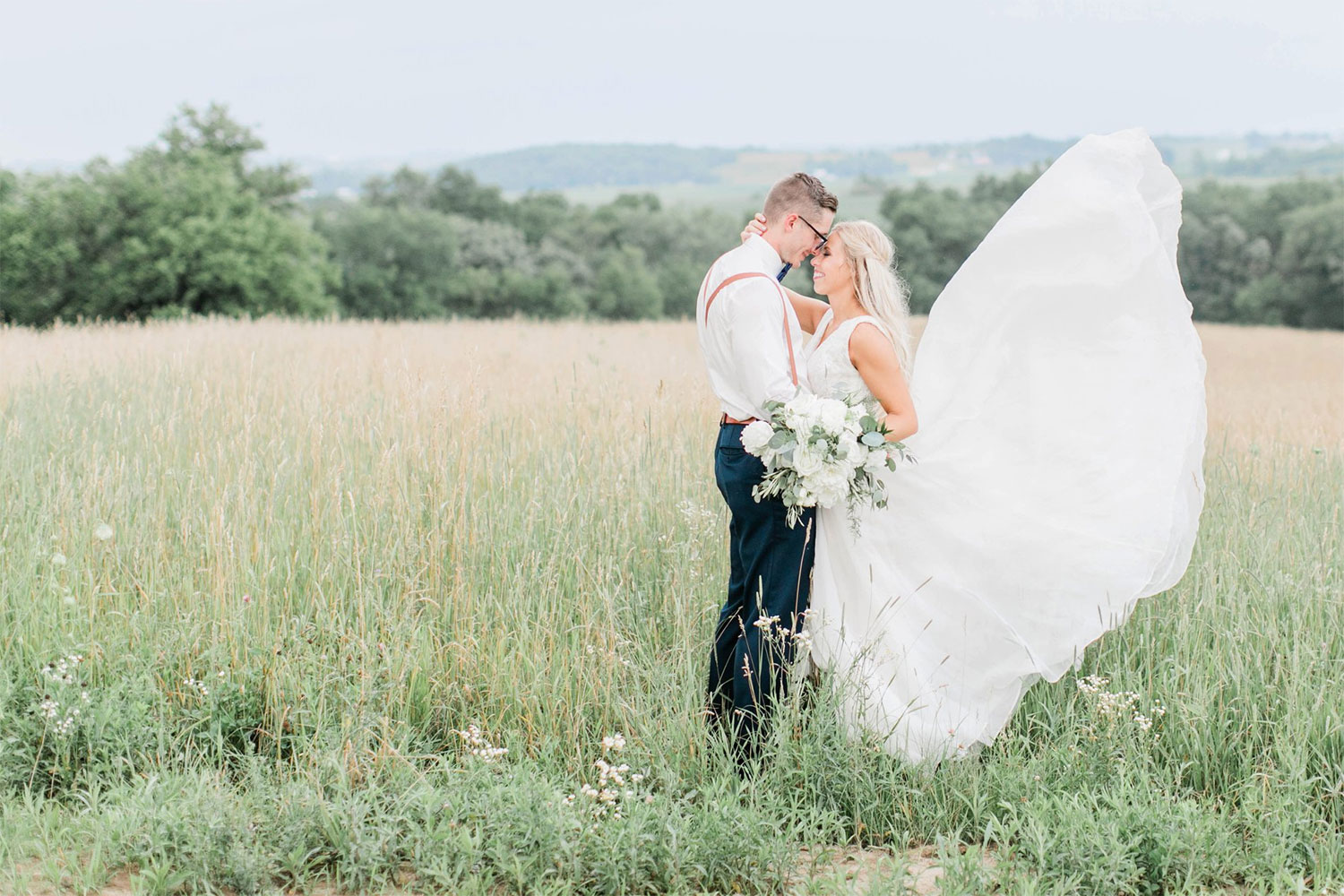 Photo of bride and groom in a tall grass field